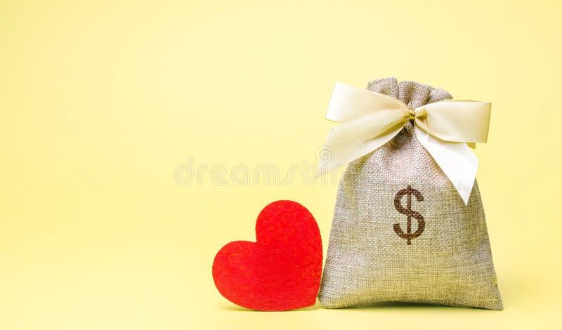 Τσάντα με τα χρήματα και την κόκκινη καρδιά βαλεντίνος ημέρας s piggy αποταμίευση τοποθέτησης χρημάτων τραπεζών συσσώρευσης Αγορά στοκ εικόνα