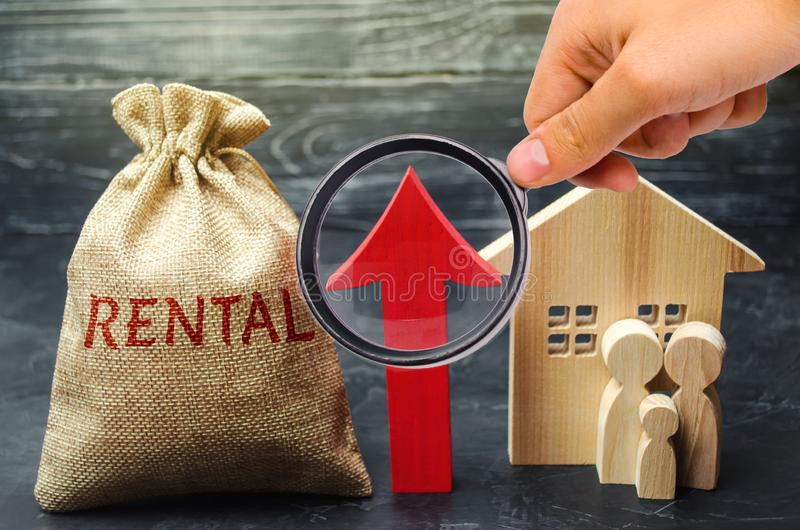 Τσάντα με τα χρήματα και το ενοίκιο λέξης και επάνω στο βέλος με την οικογένεια και το σπίτι Αύξηση του μισθώματος στην κατοικία  στοκ εικόνα
