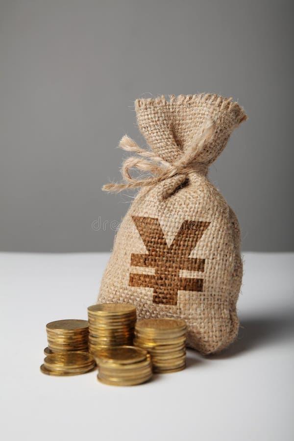 Τσάντα με τα χρήματα και yuan σκιαγραφία στο γκρίζο υπόβαθρο Σύμβολο του πλούτου και των υψηλών κερδών στοκ εικόνα