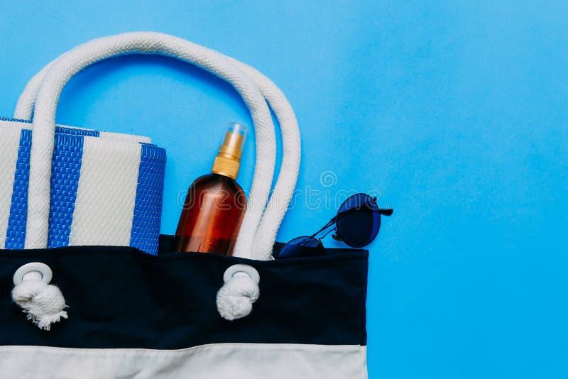 Τσάντα με τις πετσέτες, τα γυαλιά ηλίου και τα εξαρτήματα παραλιών r Κόλλα αντιγράφων, διάστημα αντιγράφων στοκ φωτογραφίες