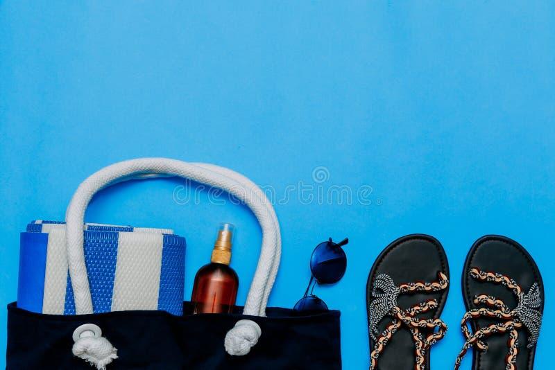 Τσάντα με τις πετσέτες, τα γυαλιά ηλίου και τα εξαρτήματα παραλιών r Κόλλα αντιγράφων, διάστημα αντιγράφων στοκ φωτογραφία