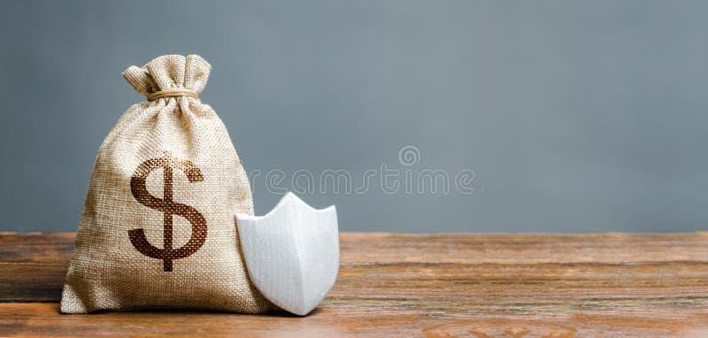 Τσάντα με το σύμβολο δολαρίων και την ασπίδα προστασίας Έννοια την προστασία των χρημάτων, που εγγυάται τις καταθέσεις Ο πελάτης  στοκ φωτογραφία