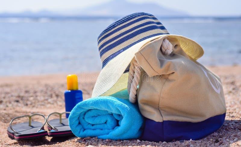 Τσάντα παραλιών και καπέλο ήλιων στην ηλιόλουστη εγκαταλειμμένη παραλία στοκ φωτογραφίες με δικαίωμα ελεύθερης χρήσης