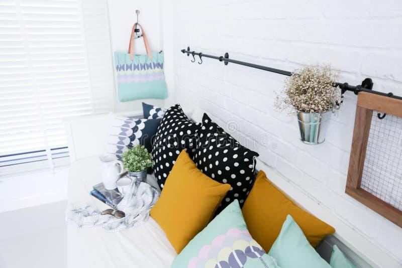 Τσάντα που κρεμιέται στον άσπρο τουβλότοιχο με τα ζωηρόχρωμα μαξιλάρια στοκ φωτογραφίες