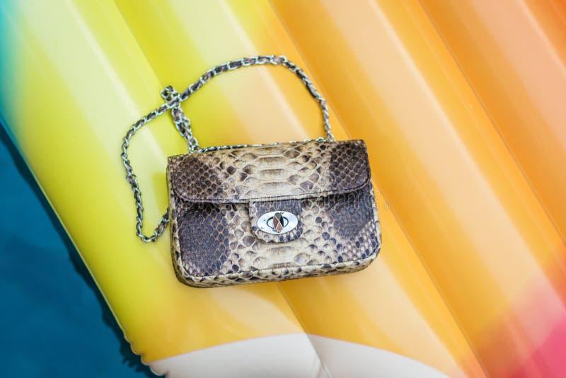 Τσάντα πολυτέλειας μόδας snakeskin python σε ένα διογκώσιμο κίτρινο στρώμα στην πισίνα Θερινή διάθεση στοκ εικόνες