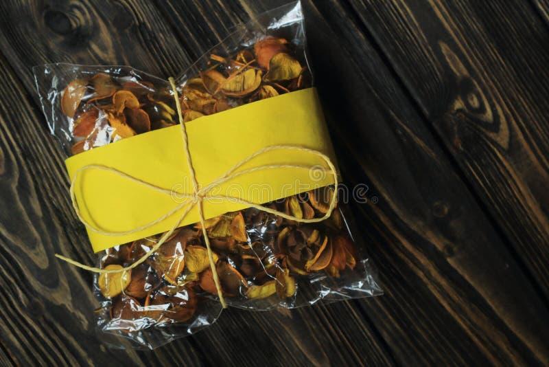 Τσάντα σελοφάν με τους ξηρούς καρπούς στο σκοτεινό ξύλινο υπόβαθρο στοκ εικόνες με δικαίωμα ελεύθερης χρήσης