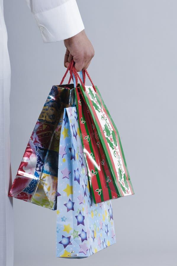 Τσάντες αγορών εκμετάλλευσης χεριών με τα δώρα στοκ φωτογραφία
