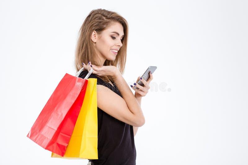 Τσάντες αγορών εκμετάλλευσης γυναικών και χρησιμοποίηση του smartphone στοκ εικόνα