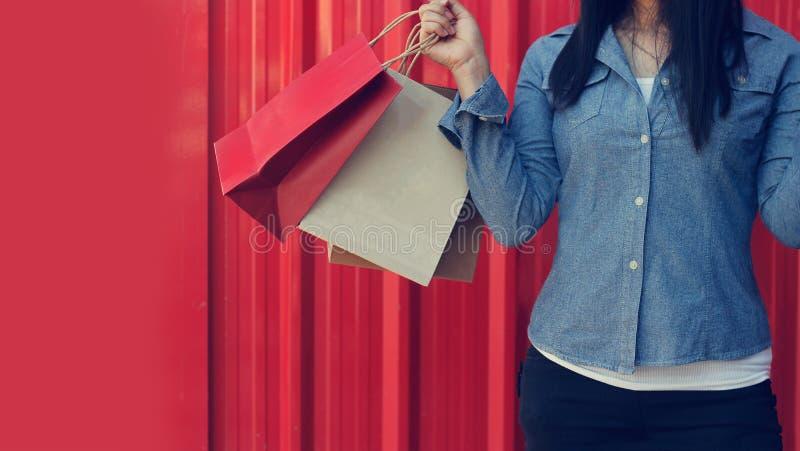 Τσάντες αγορών εκμετάλλευσης γυναικών στο κόκκινο υπόβαθρο στοκ εικόνες