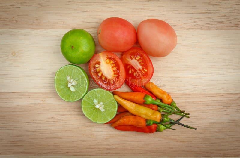 Τσίλι και ντομάτες με έναν ασβέστη σε ένα ξύλο στοκ φωτογραφία