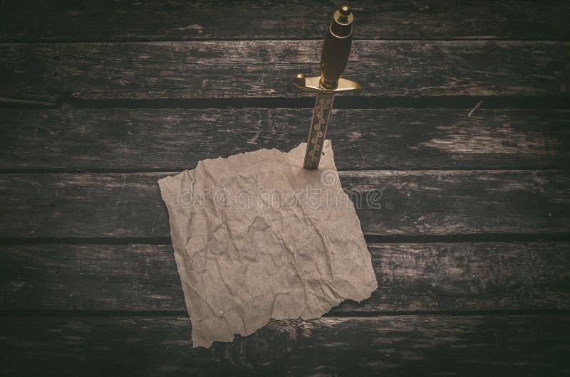 Τσαλακωμένη περγαμηνή σελίδων καφετιού εγγράφου και το στιλέτο Πίνακας πειρατών ή τυχοδιωκτών στοκ εικόνες με δικαίωμα ελεύθερης χρήσης
