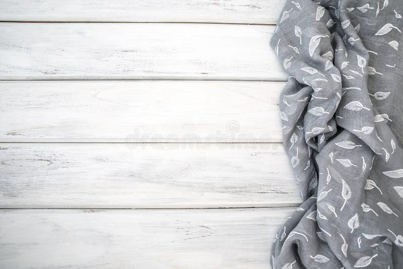 Τσαλακωμένη τραπεζομάντιλο ή πετσέτα στον κενό άσπρο ξύλινο πίνακα με στοκ εικόνες