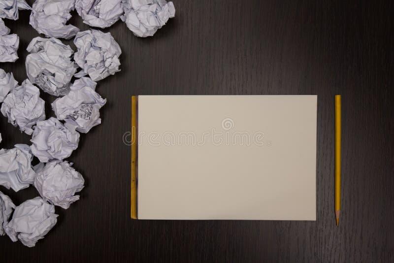 Τσαλακωμένες σφαίρες εγγράφου και κενό φύλλο του εγγράφου με το μολύβι στο μαύρο υπόβαθρο Έγγραφο wad κενό τσαλακωμένο δημιουργικ στοκ εικόνα με δικαίωμα ελεύθερης χρήσης