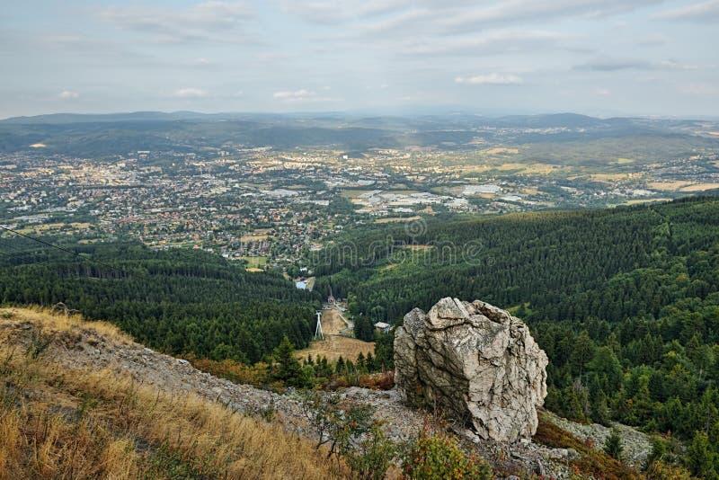 Τσεχικό τοπίο με τη μεγάλη πέτρα επάνω από την πόλη Liberec που αντιμετωπίζεται από το λόφο Jested στο ηλιοβασίλεμα θερινού βραδι στοκ φωτογραφίες με δικαίωμα ελεύθερης χρήσης
