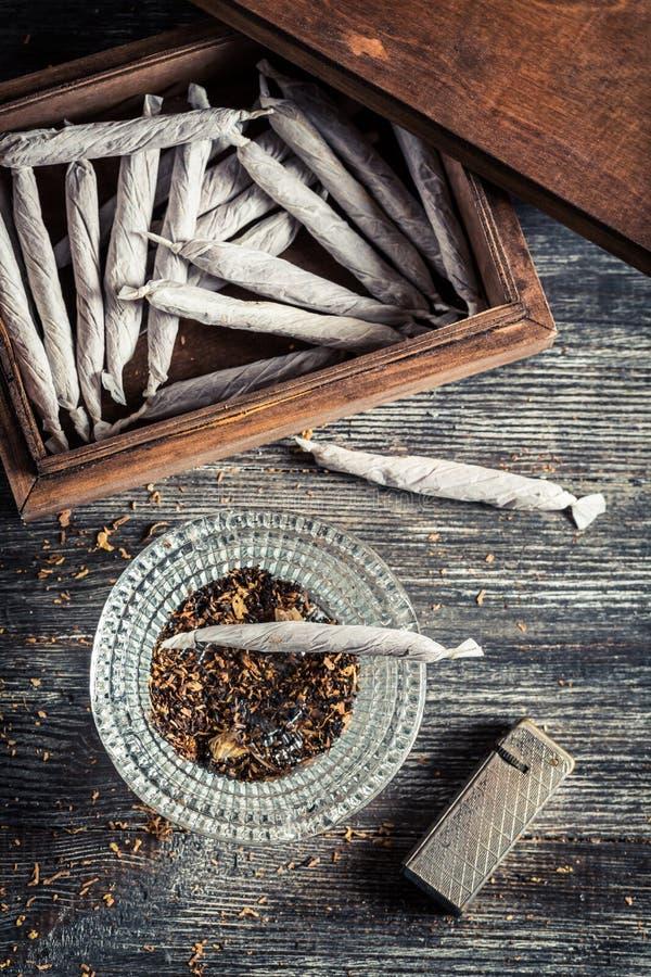 Τσιγάρα στο ξύλινους κιβώτιο, ashtray και τον αναπτήρα στοκ φωτογραφία