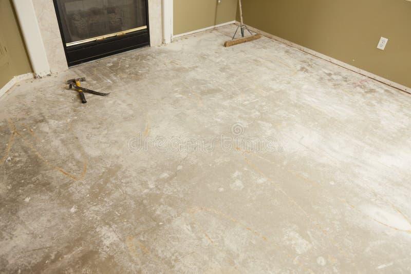 Τσιμεντένιο πάτωμα σπιτιών με τη σκούπα έτοιμη για την εγκατάσταση δαπέδων στοκ φωτογραφία