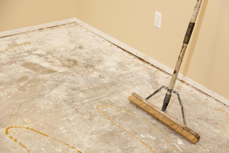 Τσιμεντένιο πάτωμα σπιτιών με τη σκούπα έτοιμη για την εγκατάσταση δαπέδων στοκ εικόνες