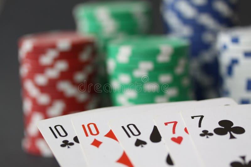 Τσιπ και κάρτες πόκερ που παρουσιάζουν το πλήρες σπίτι με 10 και άσσο στενό σε επάνω στοκ εικόνες