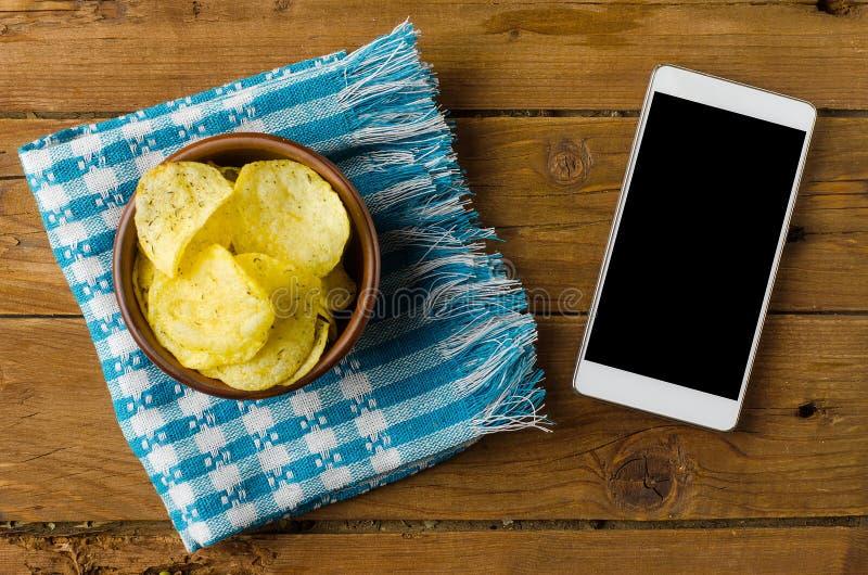 Τσιπ πατατών σε ένα κύπελλο σε έναν ξύλινο πίνακα και ένα smartphone στοκ εικόνες