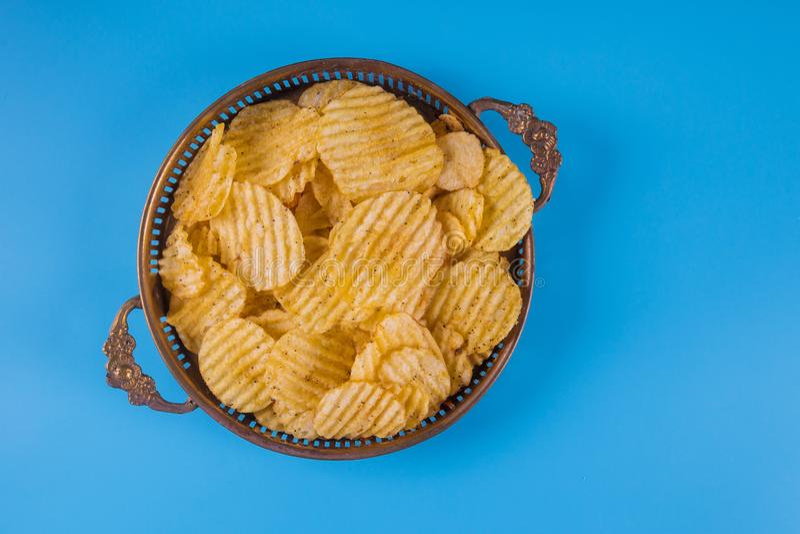 Τσιπ πατατών στα ασημένια κύπελλα στο μπλε στοκ εικόνα