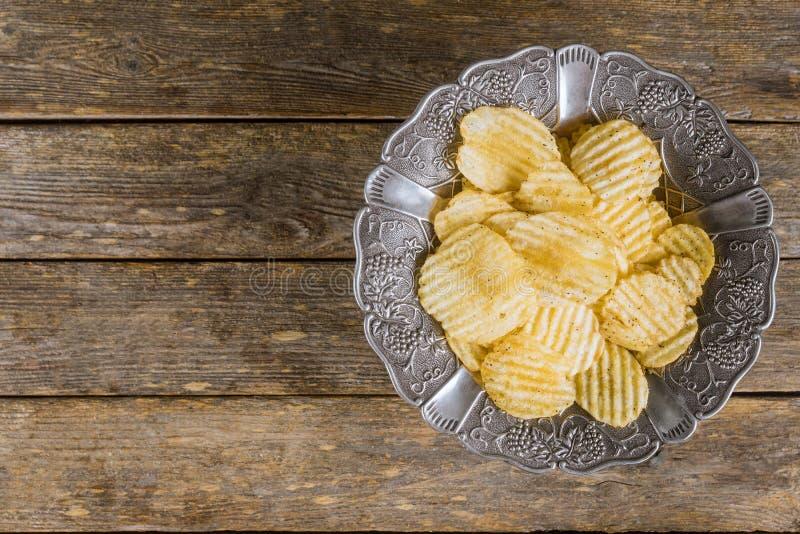 Τσιπ πατατών στο ασημένιο εκλεκτής ποιότητας πιάτο στο ξύλινο υπόβαθρο στοκ εικόνες με δικαίωμα ελεύθερης χρήσης
