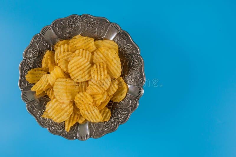 Τσιπ πατατών στο ασημένιο κύπελλο σε ένα μπλε υπόβαθρο, τοπ άποψη στοκ εικόνα