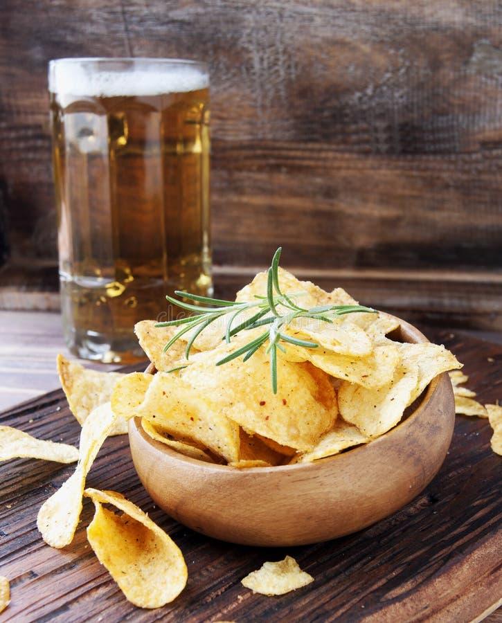 Τσιπ σε ένα ξύλινες κύπελλο και μια μπύρα στοκ εικόνες