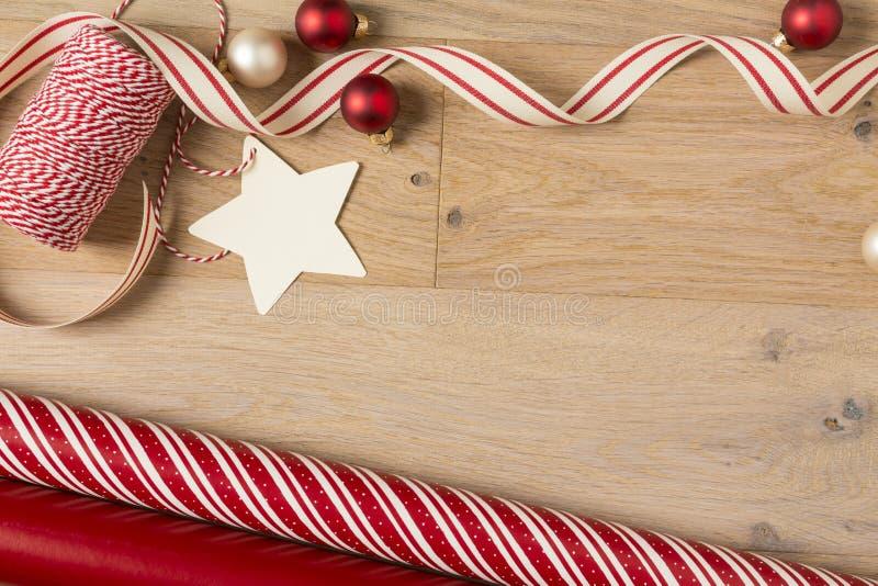 Τυλίγοντας έγγραφο δώρων Χριστουγέννων και προμήθειες κορδελλών στο ξύλινο υπόβαθρο στοκ εικόνες