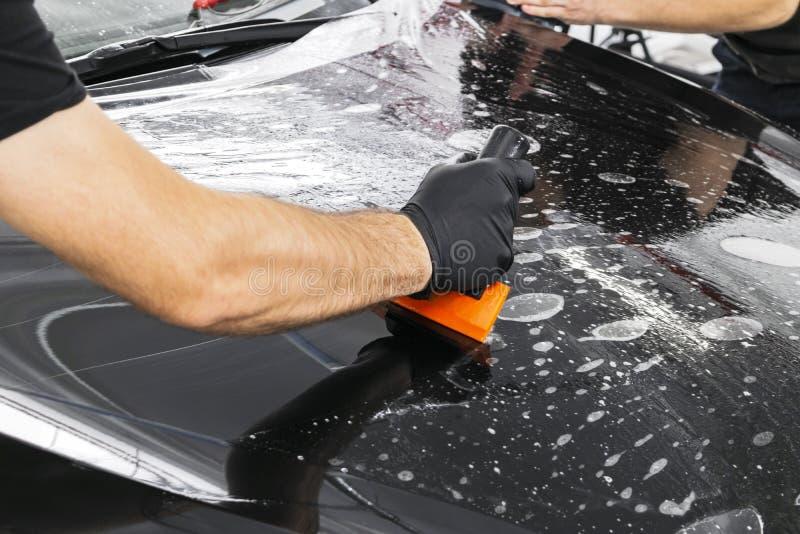 Τυλίγοντας ειδικός αυτοκινήτων που βάζει το βινυλίου φύλλο αλουμινίου ή την ταινία στο αυτοκίνητο Προστατευτική ταινία στο αυτοκί στοκ φωτογραφία με δικαίωμα ελεύθερης χρήσης