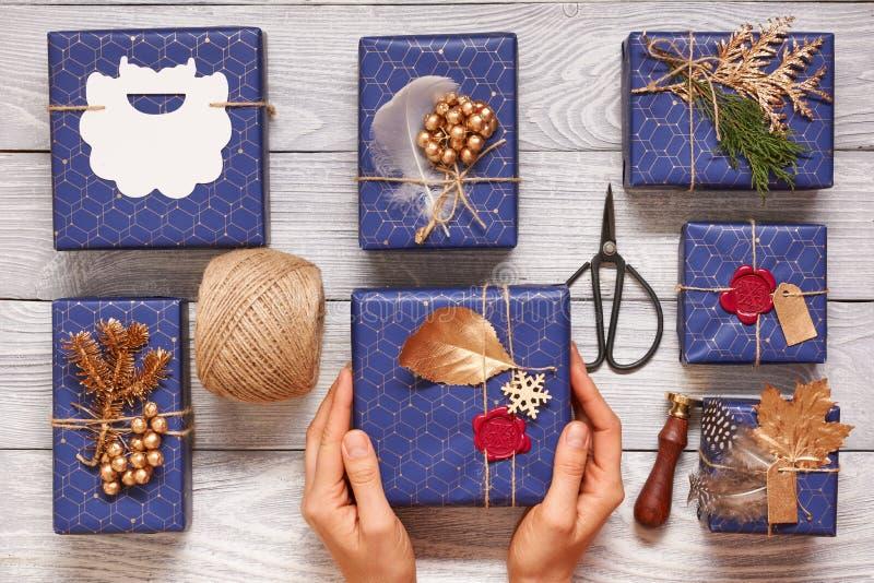 Τυλίγοντας χριστουγεννιάτικα δώρα γυναικών πέρα από το ξύλινο υπόβαθρο στοκ εικόνες