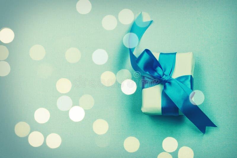 Τυλιγμένο κιβώτιο δώρων με το μπλε τόξο, στο υπόβαθρο σύστασης εγγράφου στοκ φωτογραφία