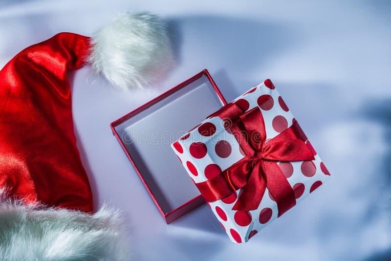 Τυλιγμένο κιβώτιο δώρων Santa καπέλο στην άσπρη επιφάνεια στοκ φωτογραφία με δικαίωμα ελεύθερης χρήσης