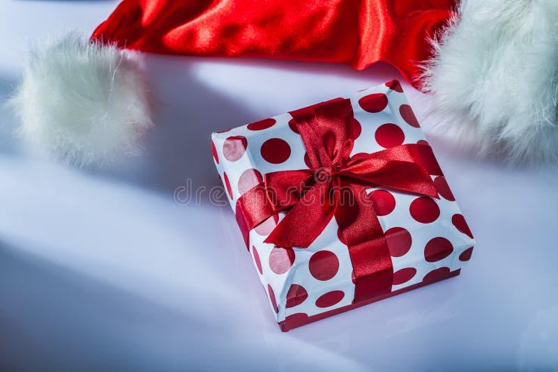 Τυλιγμένο κιβώτιο δώρων Santa ΚΑΠ στην άσπρη επιφάνεια στοκ εικόνα με δικαίωμα ελεύθερης χρήσης