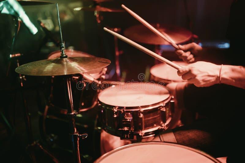Τυμπανιστής που παίζει την εξάρτηση τυμπάνων του στη συναυλία στη λέσχη στοκ φωτογραφίες
