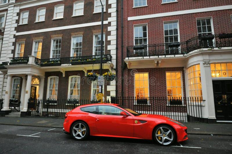 Τυπικό σπίτι στο Mayfair London με κόκκινο αυτοκίνητο συγκομιδής Ferrari στοκ εικόνες