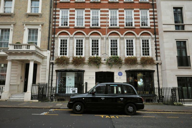 Τυπικό σπίτι στο Mayfair London με τυπικό μαύρο ταξί στοκ εικόνες