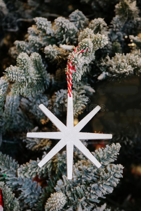 Τυποποιημένη απλή snowflake διακόσμηση με τα σπινθηρίσματα που κρεμά σε ένα συγκεντρωμένο χριστουγεννιάτικο δέντρο στοκ εικόνες με δικαίωμα ελεύθερης χρήσης