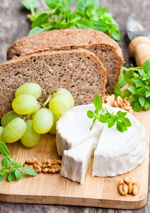 Τυρί αιγών με τα φρούτα και ολόκληρο το ψωμί σιταριού στοκ εικόνα με δικαίωμα ελεύθερης χρήσης