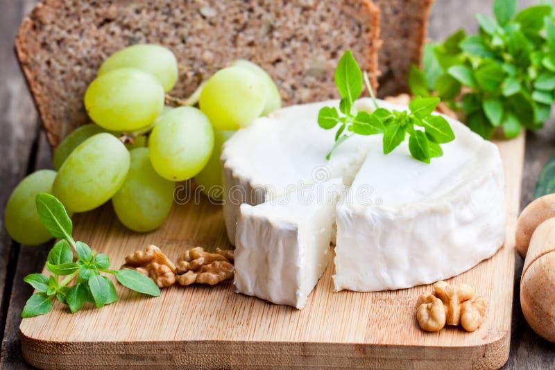 Τυρί αιγών με τα φρούτα και ολόκληρο το ψωμί σιταριού στοκ εικόνες