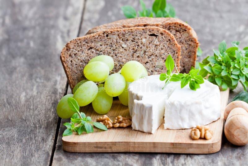 Τυρί αιγών με τα φρούτα και ολόκληρο το ψωμί σιταριού στοκ φωτογραφίες