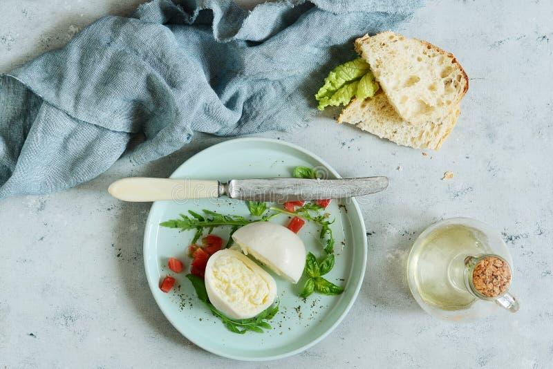 Τυρί βούβαλων μοτσαρελών σε ένα πιάτο γευμάτων με τα φύλλα salsa ντοματών του arugula και το βασιλικό με το ελαιόλαδο σε ένα γκρί στοκ φωτογραφίες με δικαίωμα ελεύθερης χρήσης
