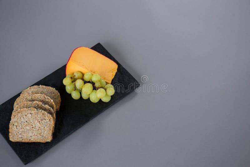 Τυρί γκούντα, σταφύλια και καφετιές φέτες ψωμιού στο πιάτο πλακών στοκ εικόνα με δικαίωμα ελεύθερης χρήσης
