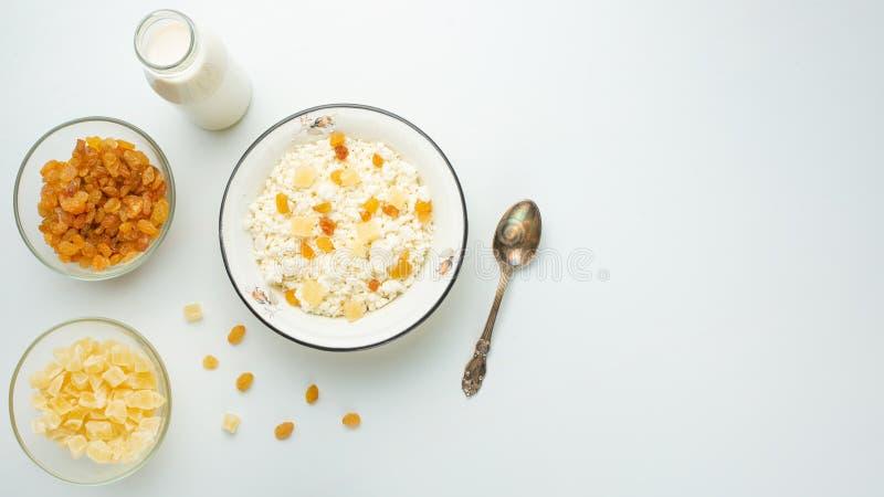 Τυρί εξοχικών σπιτιών με τις σταφίδες και τα κολοκύθια ανανά, με το γάλα σε ένα κύπελλο σε έναν άσπρο πίνακα Νόστιμων και υγιών τ στοκ εικόνα με δικαίωμα ελεύθερης χρήσης