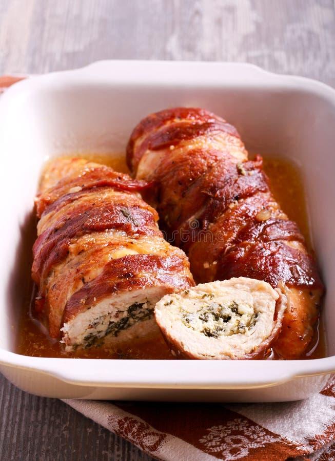 Τυρί και γεμισμένο σπανάκι στήθος κοτόπουλου που τυλίγονται στο μπέϊκον στοκ εικόνες