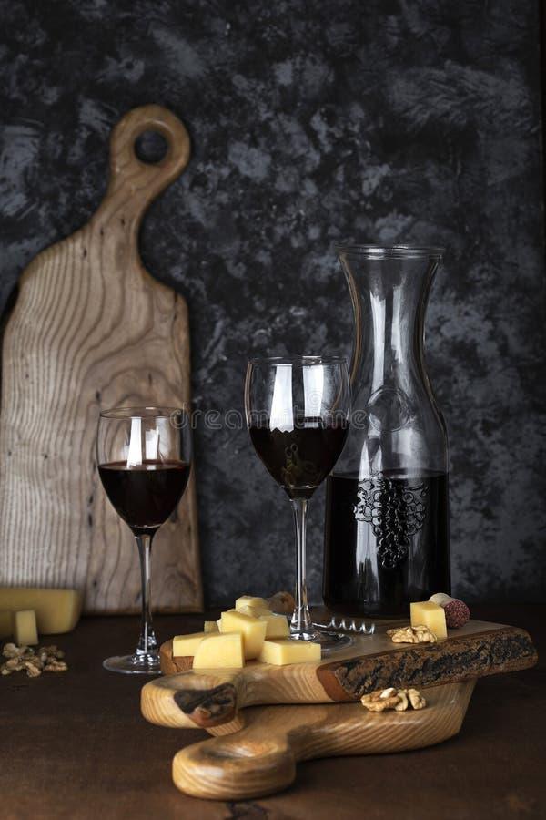 Τυρί και δύο ποτήρια του κρασιού στον ξύλινο πίνακα στοκ φωτογραφία με δικαίωμα ελεύθερης χρήσης