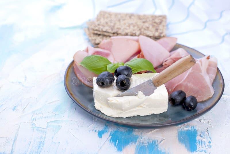 Τυρί και ζαμπόν με τις ελιές σε ένα γκρίζο πιάτο Άσπρο υπόβαθρο με τα μπλε διαζύγια Μαχαίρι για το τυρί Ξηρό Breadstones Ελεύθερο στοκ φωτογραφίες με δικαίωμα ελεύθερης χρήσης