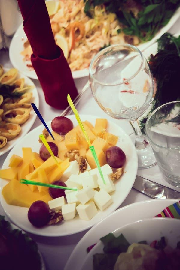 Τυρί και σταφύλια σε ένα πιάτο στον εξυπηρετούμενο πίνακα στοκ εικόνες