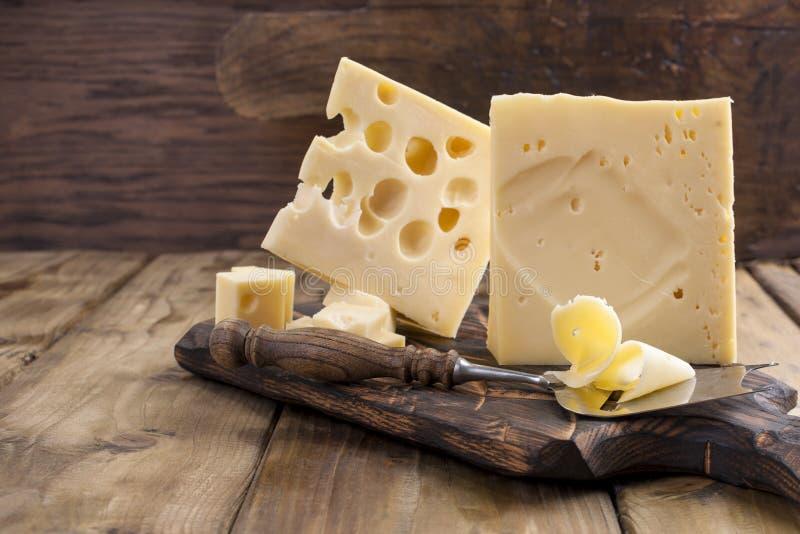 Τυρί με τις τρύπες μεγάλες και μικρές Ξύλινοι πίνακας και μαχαίρι Παραδοσιακό ολλανδικό τυρί διάστημα αντιγράφων στοκ φωτογραφία