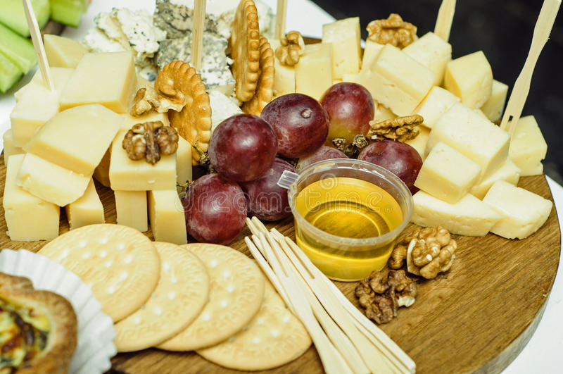Τυρί μιγμάτων στον ξύλινο πίνακα με τα σταφύλια Μπροστινή όψη στοκ εικόνες