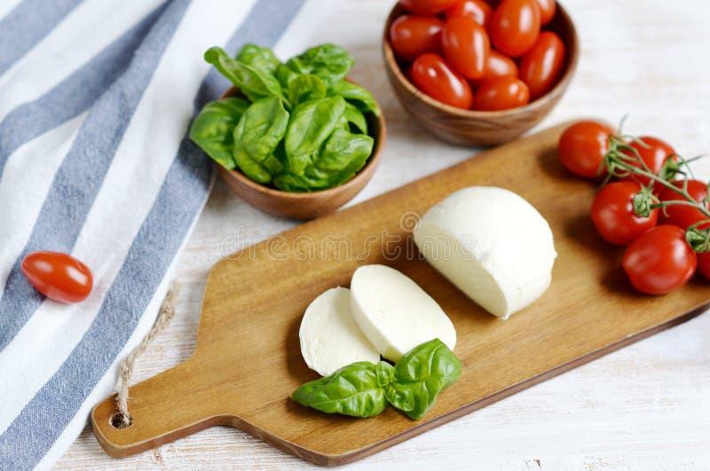 Τυρί μοτσαρελών με τις κόκκινα ντομάτες και τα φύλλα βασιλικού, πιπέρι, ελαιόλαδο στοκ εικόνα με δικαίωμα ελεύθερης χρήσης